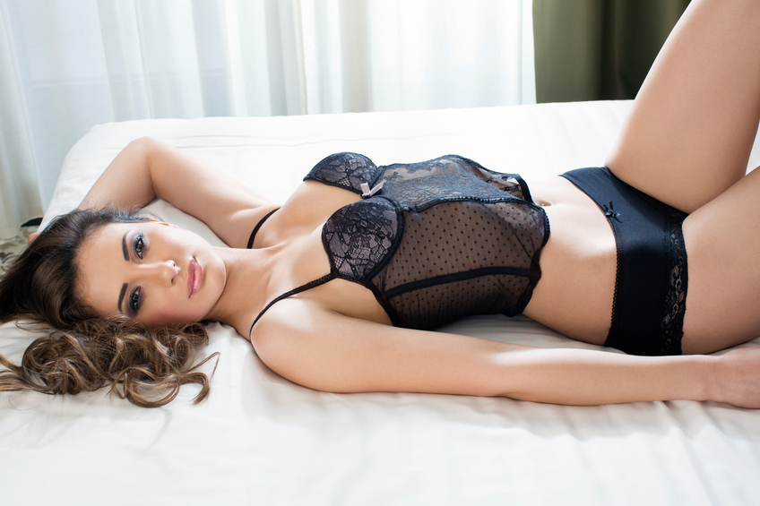 Beautiful woman posing in bed in lingerie