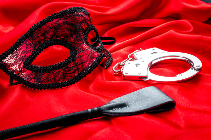 BDSM concept image with a mask, hand cuffs and a flogger / whip covered in rose petals on red silk. BDSM is a variety of erotic practices or role playing involving bondage, dominance and submission, sadomasochism