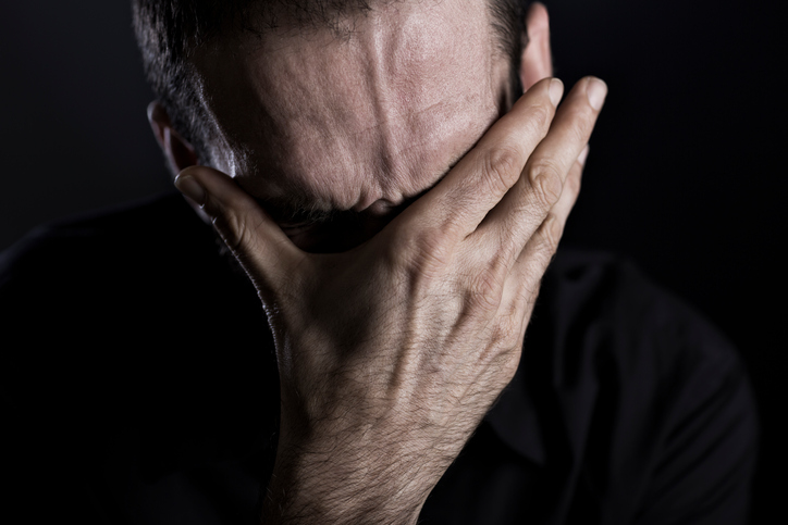 Close up of miserable man burying face in hands, looking desperate, isolated on black background.