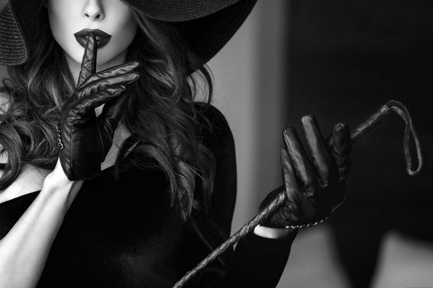 Woman in hat and whip showing no talk, black and white