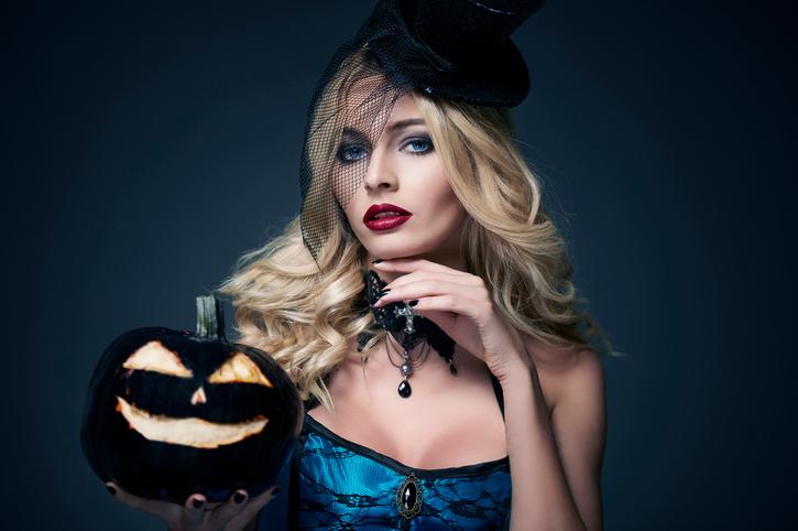 Magic blonde female witch with pumpkin