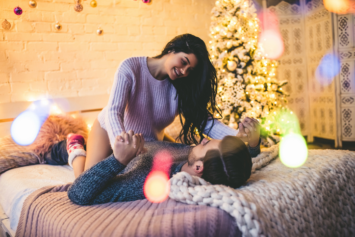 Passionate romantic couple spending time before New Year near beautiful Christmas tree at home. Sexy young woman and handsome man are lying on bed in sweaters and hugging. Tender couple sleep together