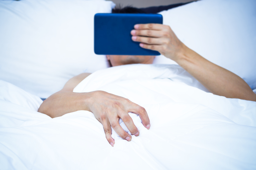 Young man lying on bed watching pornography on tablet