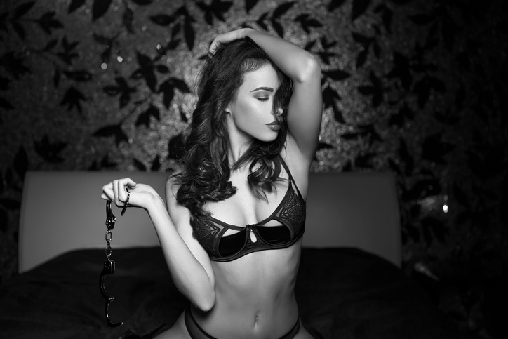 A sexy woman sits on a bed holding handcuffs