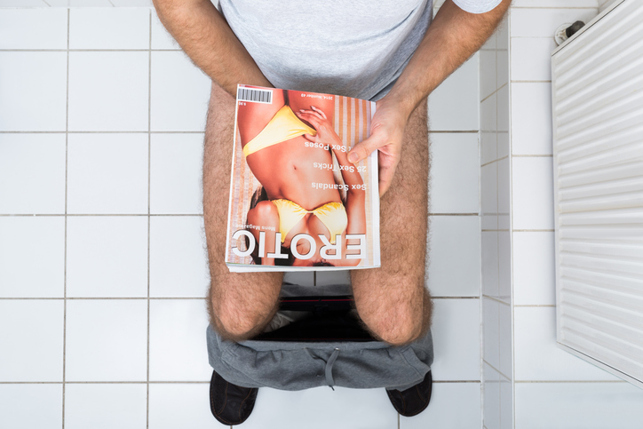 High Angle View Of A Man In Toilet With Sexy Magazine