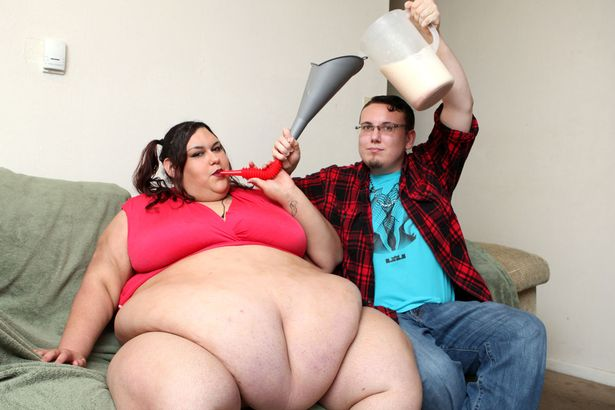Fat woman being fed through a funnel