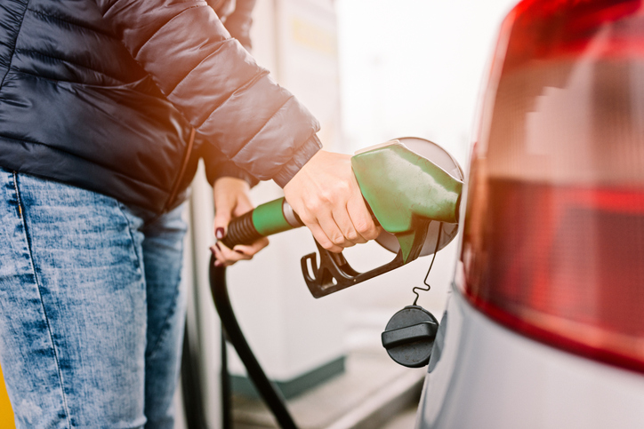 Woman refueling her small silver car at the gasoline station
