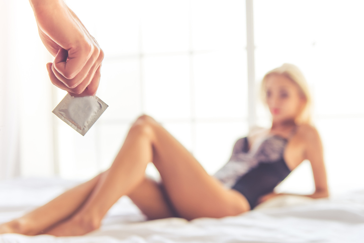 Cropped image of man's hand holding a condom, sexy woman is lying on bed in the background