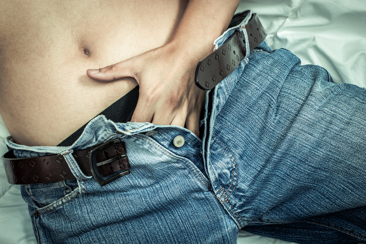 Playful male left hand touching his panties under blue jeans on bed