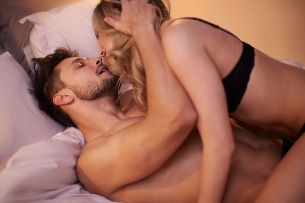 A sexy couple in bed using cowgirl position