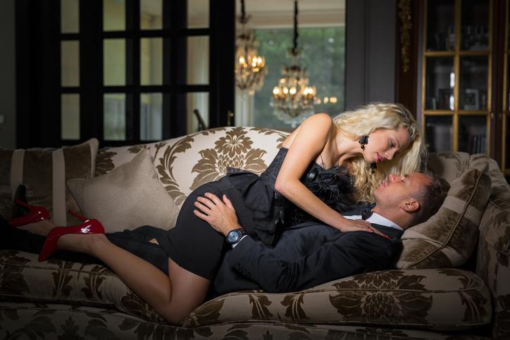 Fancy woman in black dress lying on top of man