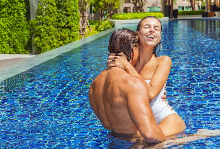 Happy couple bathing together in swimming pool