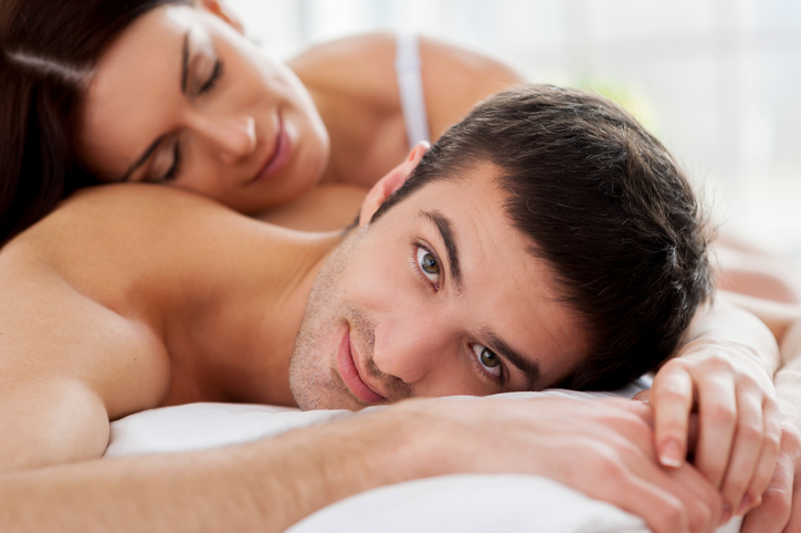 Cheerful young loving couple lying in bed and smiling at camera