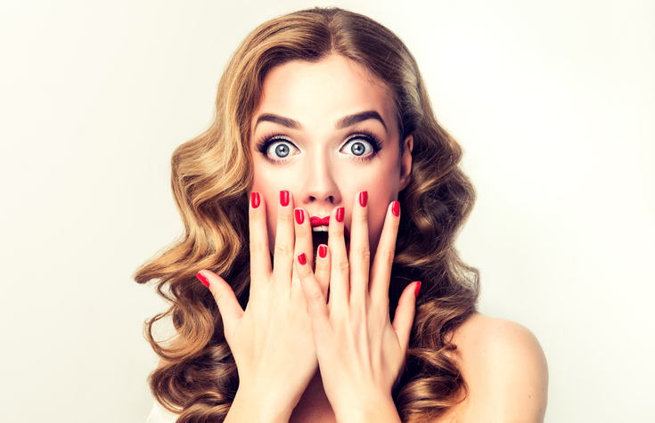 Expression of shock and amazement on face of perfectly looked, young, beautiful woman. Pin-up style make up, and red manicure.