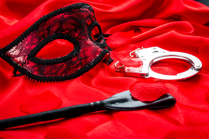 BDSM concept image with a eye mask, hand cuffs and a flogger / whip covered in rose petals on red silk covered in rose petals. BDSM is a variety of erotic practices or role playing involving bondage, dominance and submission, sadomasochism