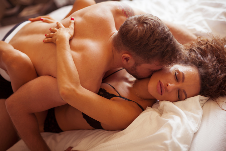 People in love making love in bedroom.