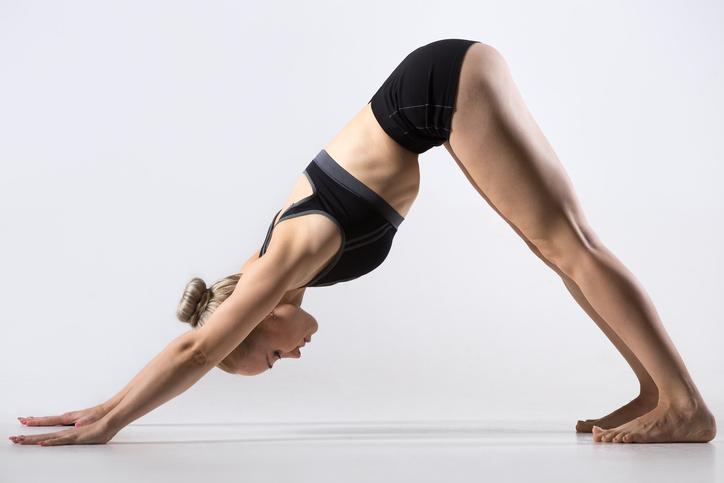 Sporty beautiful young woman practicing yoga, doing downward facing dog pose, adho mukha svanasana (sun salutation exercise), working out wearing black sportswear, studio, full length, side view