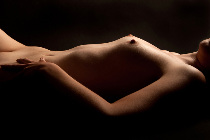 Naked torso of a beautiful young woman, recumbent in front of black background