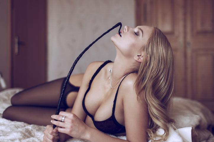 Sexy blonde woman in underwear biting whip