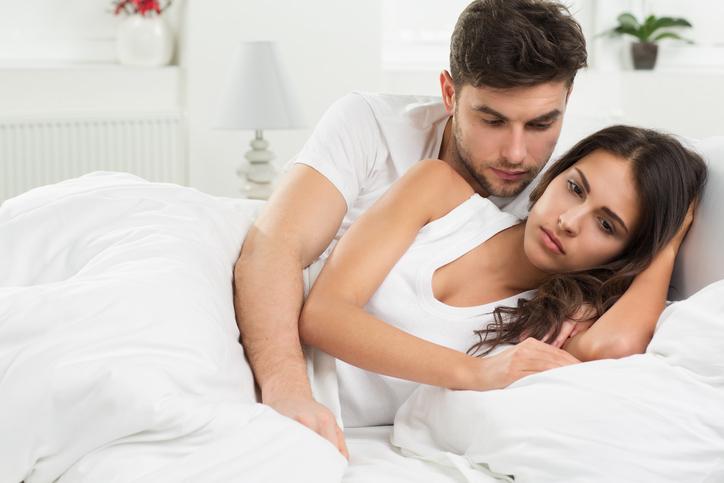 portrait of unhappy young heterosexual couple in bedroom