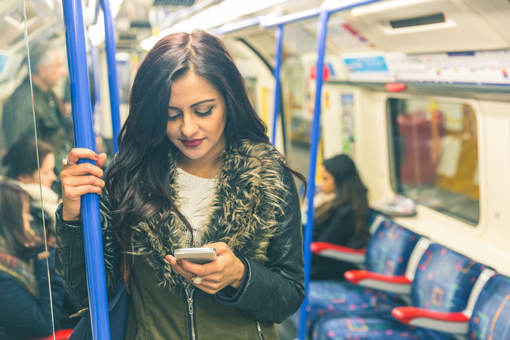 Teenager looks at phone on train