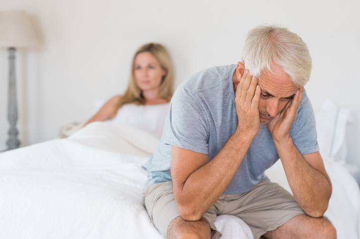Unhappy man on edge of bed with upset wife in it