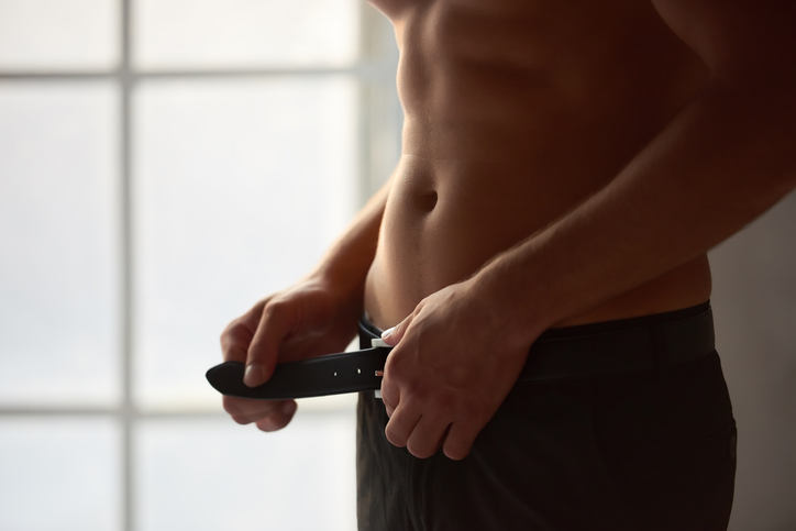 Man unbuckling belt. Attractive male body close up