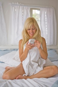Nude woman playing with phone on her bed