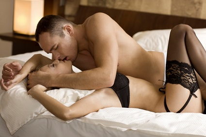 Man on top of a woman in bed, kissing her