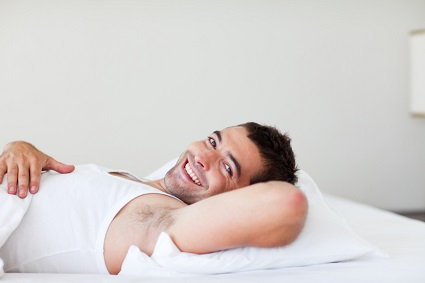 Handsome man lying in bed smiling