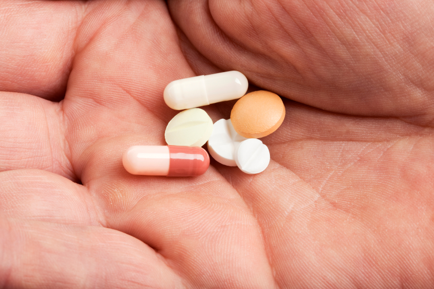 daily dose of medicine - various pills, tablets and capsules on the palm of a male hand