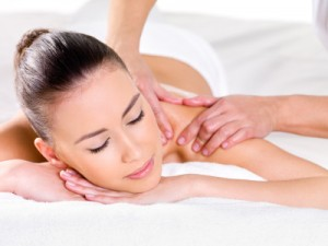 Woman leans forward being massaged
