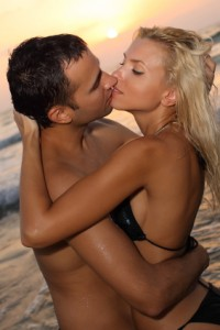Man and blonde woman kissing on a beach