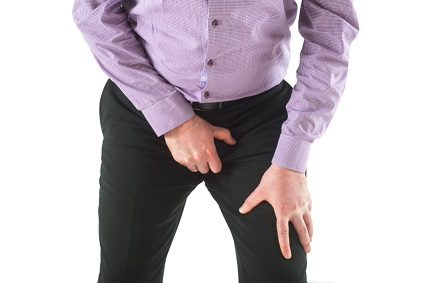 Guy holding his balls through trousers
