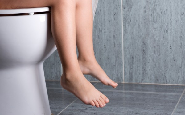 Legs of woman on white toilet