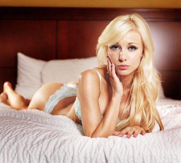 Blonde girl leans forward on bed