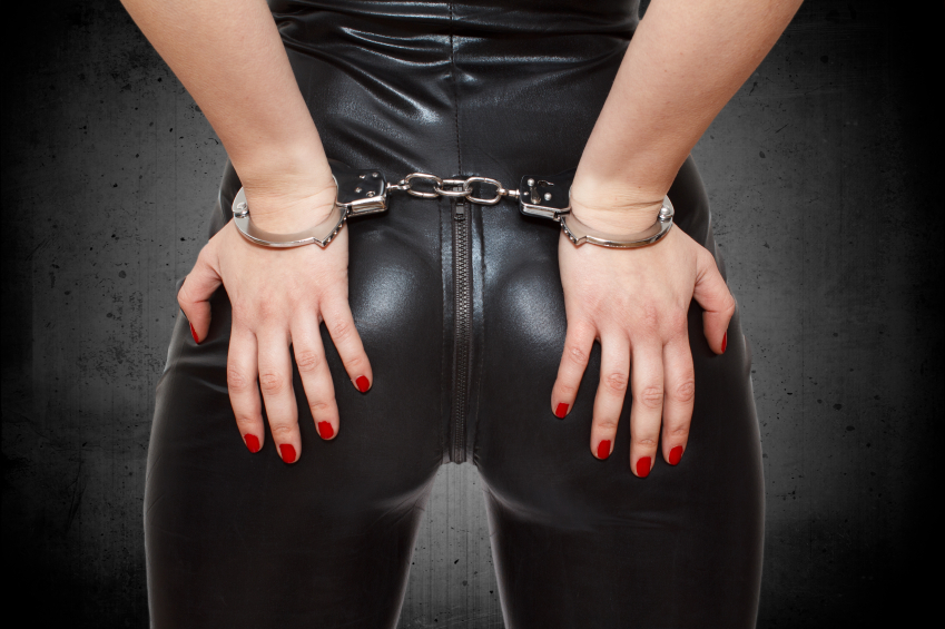 Sexy dominatrix hands on ass in handcuffs, eager to try a little kink