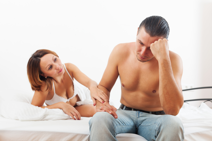 Man sits on side of bed looking stressed, woman looks at him