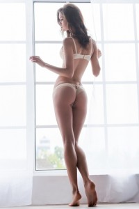 Confident in her perfect body. Full length rear view of beautiful young woman in lingerie standing near the window