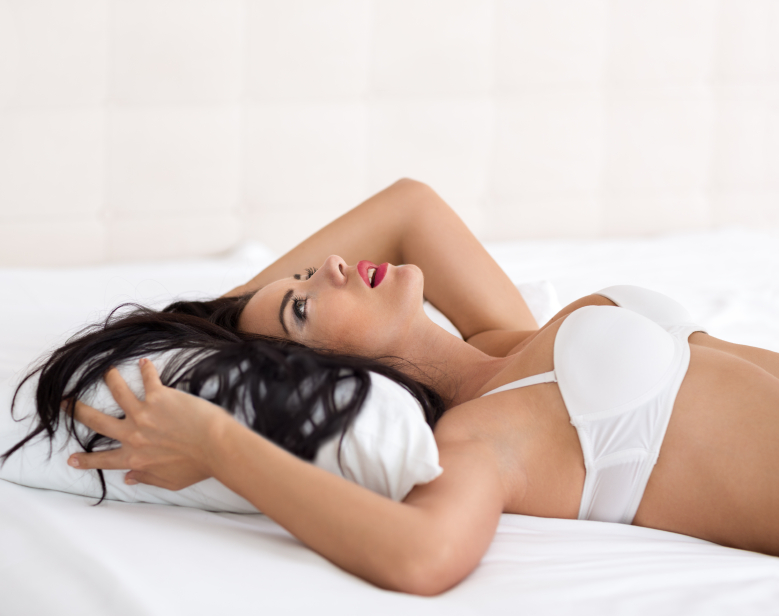 Woman in white bra on back in bed looking happy
