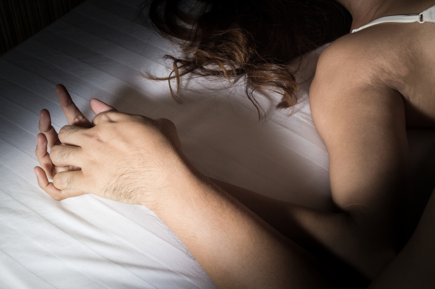 Couples hands interlocked on a bed