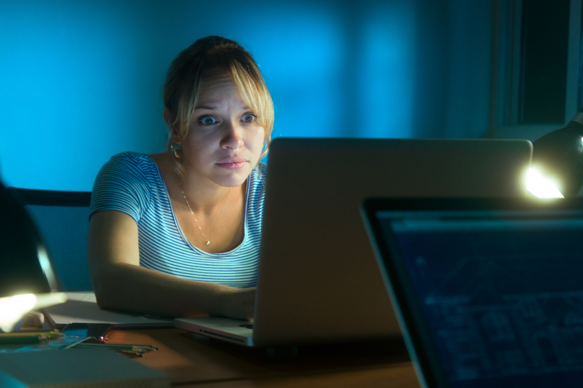 A woman sitting at a computer looking shocked