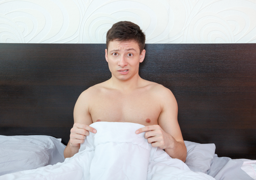 Man looking down underneath sheets at his genitals