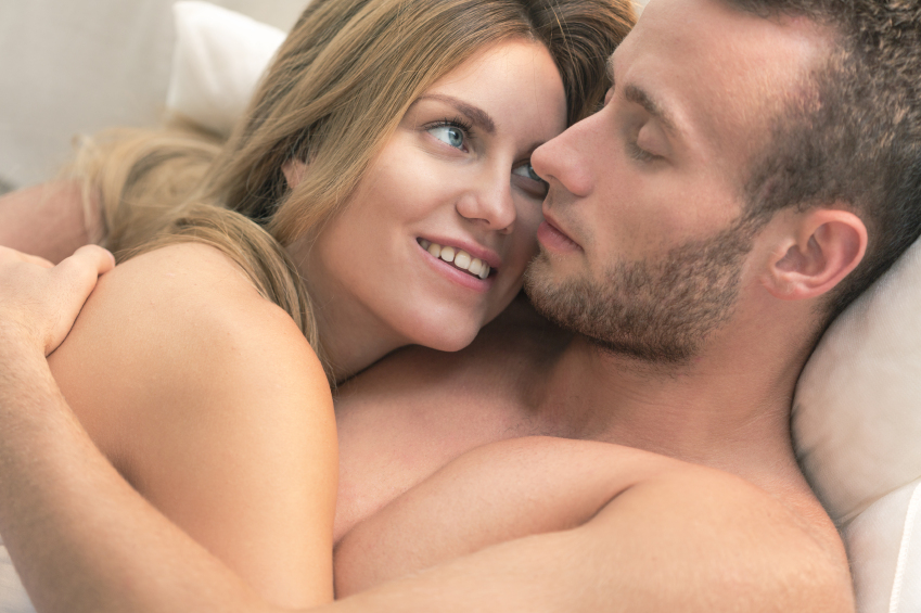 Man and escort embrace in bed