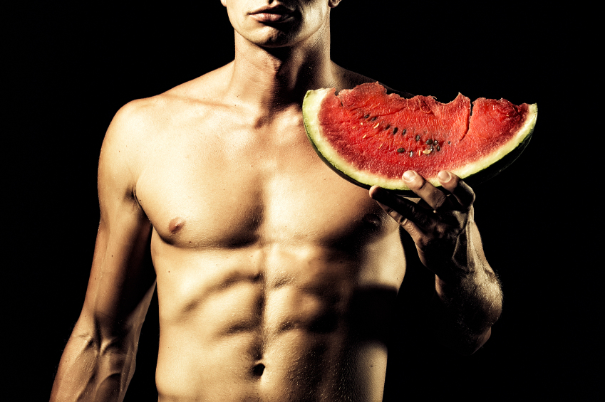 Young sexual naked man with beautiful strong muscular body holding big juicy red water melon slice standing on black background, horizontal picture