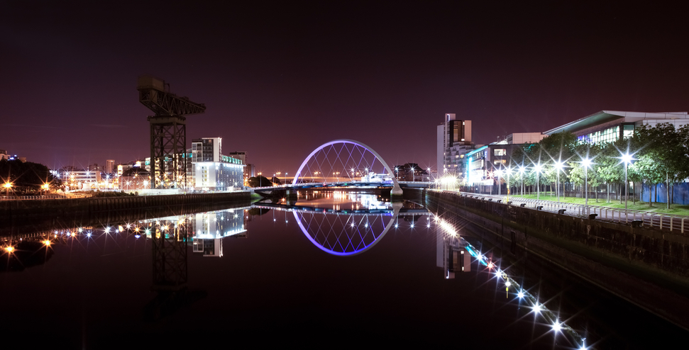 The reflection of Glasgow's Arc bridge is captured in still water at night in this wide panorama over the river Clyde.