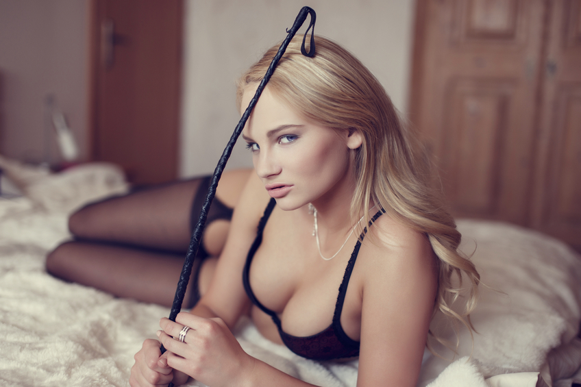 Sexy blonde woman holding whip on bed