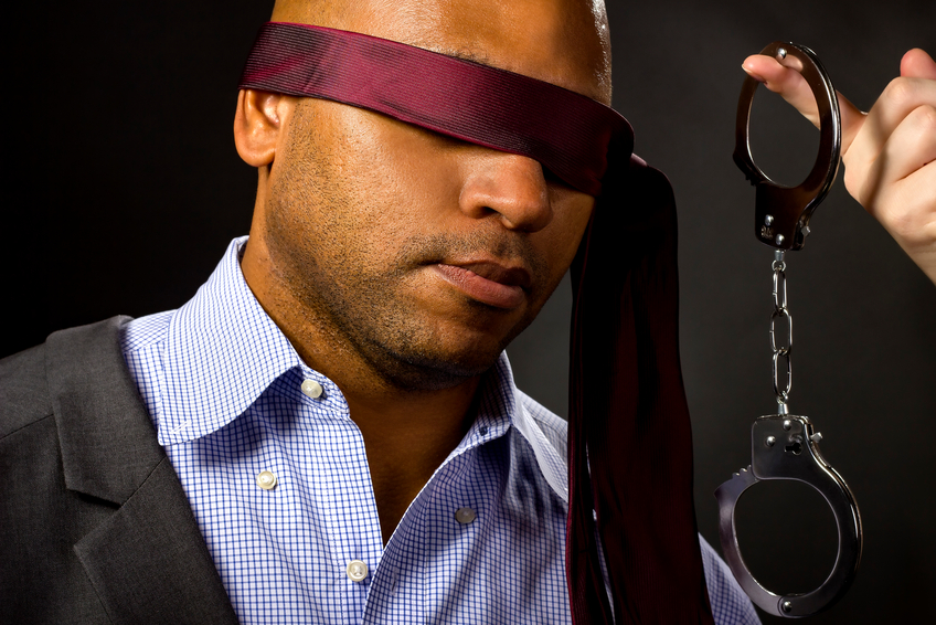 Black man in blindfold whilst handcuffs are waived at him