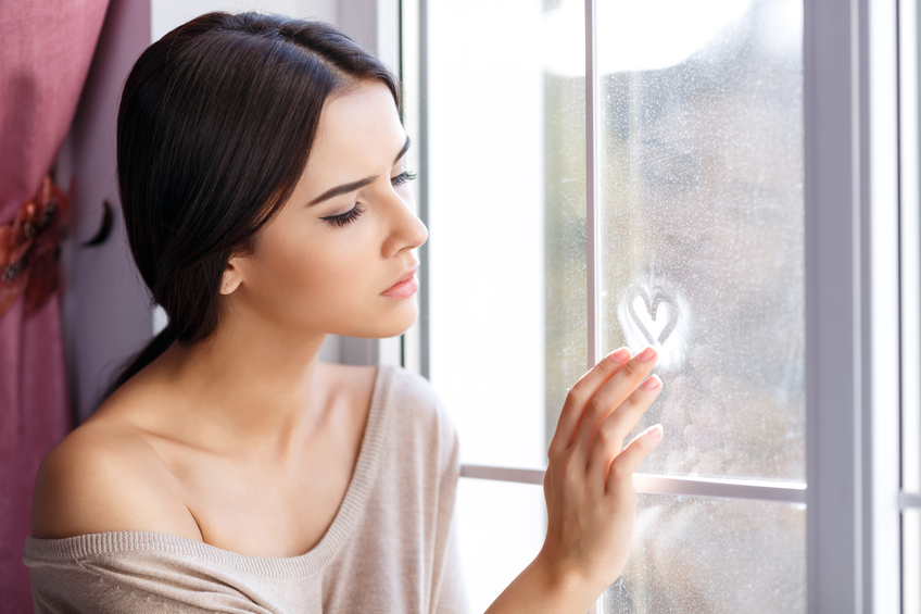 Woman looking sad at a window