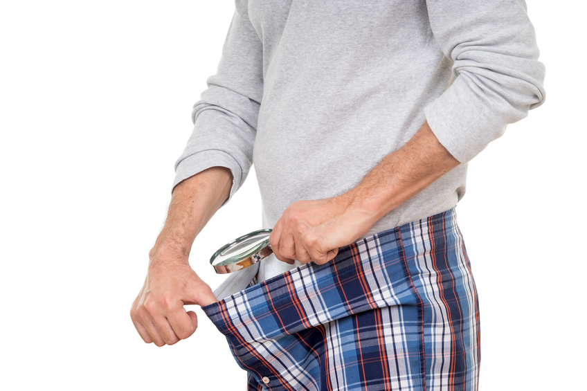 Man with magnifying glass looking into his boxer short